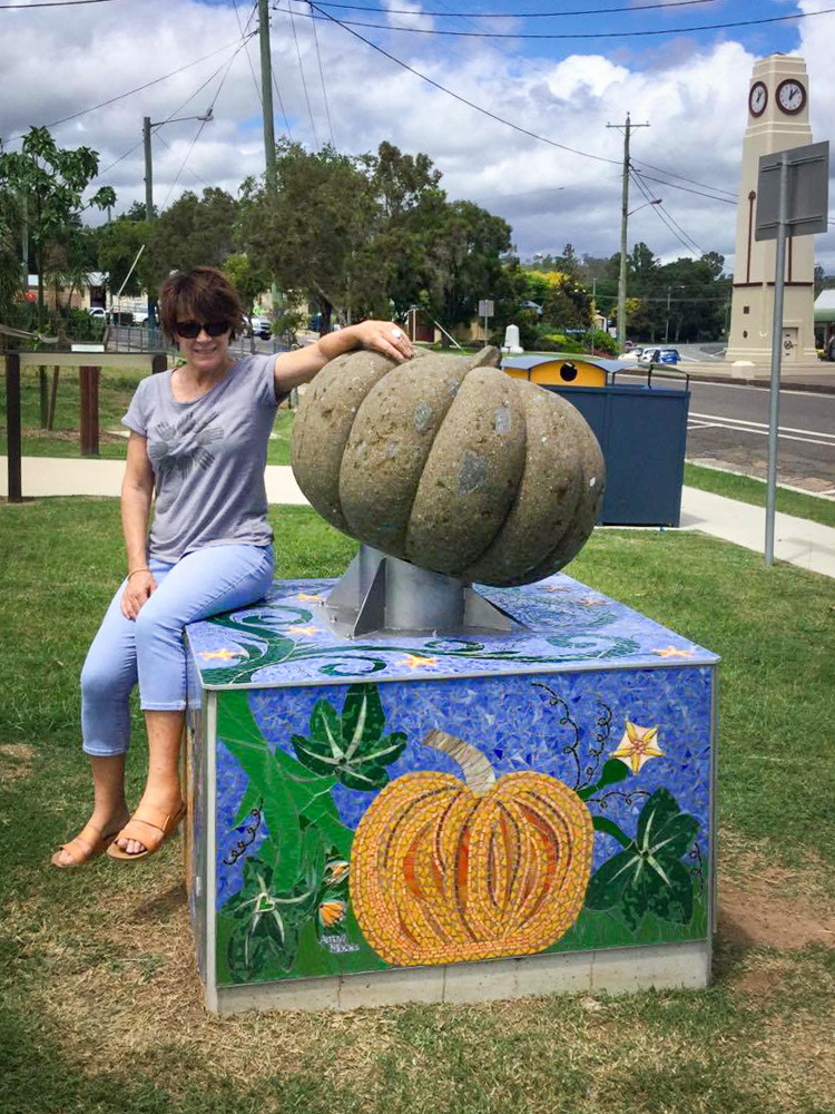 Heather May poses on her mosaiced plinth in Goomeri Qld
